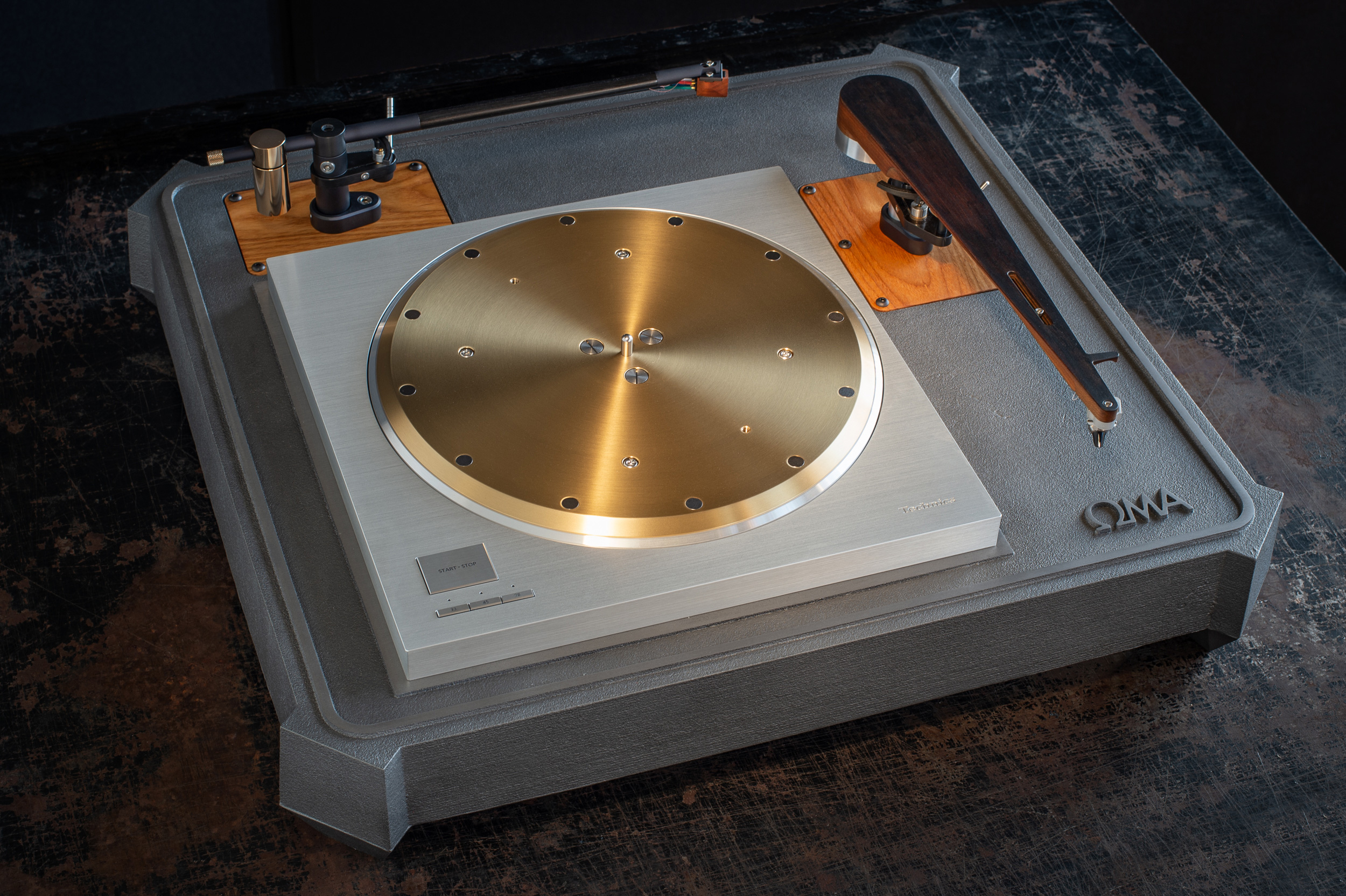 "We also offer the OMA SP10R plinth system in a two arm configuration. This substantially increases the size, weight and cost- 23"" depth x 25"" width x 5"" height (top of platter). Shown here with Schroeder CB and Model B tonearms."
